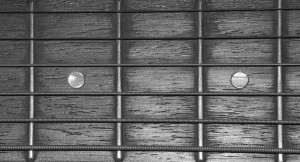 A close up of an acoustic guitar, and it's strings. (Black and white)